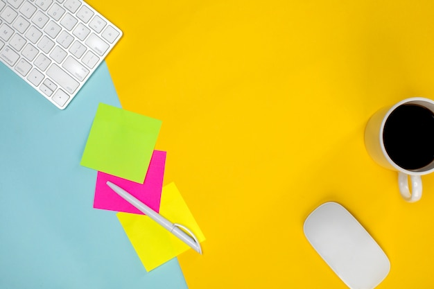 Vários dispositivos sem fio na mesa amarela e papel colorido