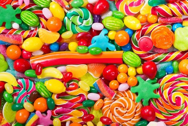 Vários doces coloridos, geleias, pirulitos e geleias como pano de fundo, vista de cima