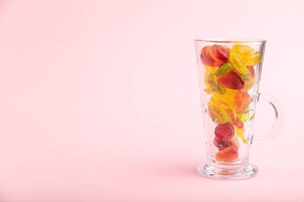Vários doces de geleia de frutas em um copo com fundo rosa pastel
