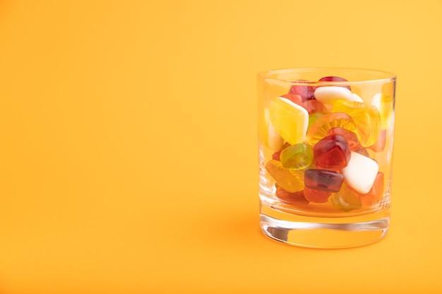 Vários doces de geleia de frutas em um copo em fundo laranja pastel