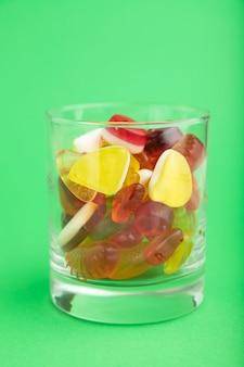 Vários doces de geleia de frutas em um copo sobre fundo verde pastel