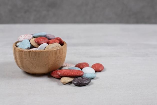 Vários doces de pedra coloridos em uma tigela de madeira.