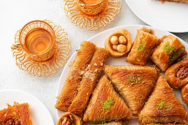 Vários doces turcos e uma xícara de chá no plano de fundo texturizado branco