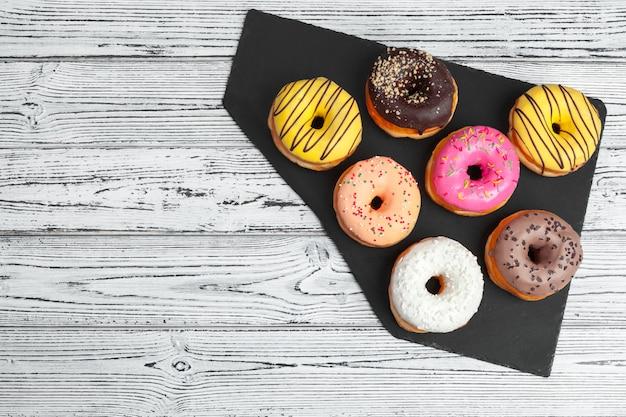 Vários donuts frescos em um prato de cerâmico preto em uma mesa de madeira