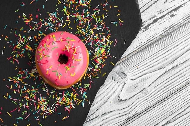 Vários donuts frescos em uma placa de cerâmica preta em uma mesa de superfície de madeira
