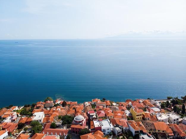 Vários edifícios com telhados laranja, localizados na costa do mar egeu