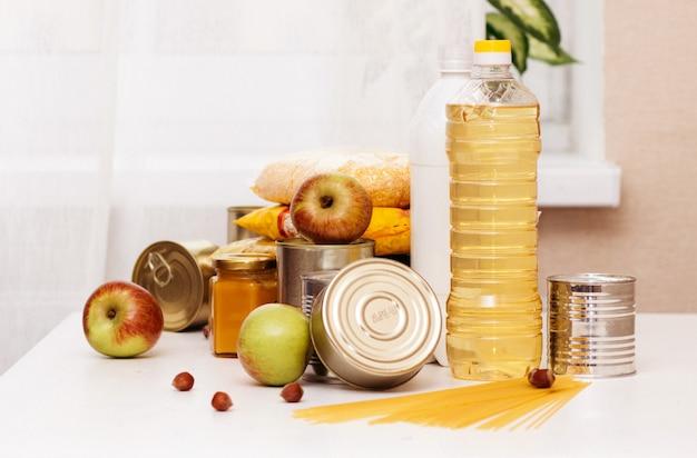 Vários enlatados, massas e cereais em uma mesa branca. doação de alimentos ou conceito de entrega de alimentos.