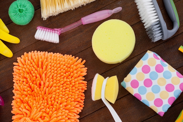 Vários equipamentos de limpeza dispostos no piso de madeira