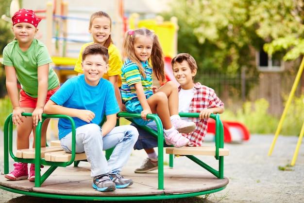 Vários estudantes que têm o divertimento no carrossel