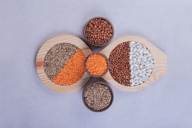 Vários feijões crus e lentilhas em tigelas de madeira.