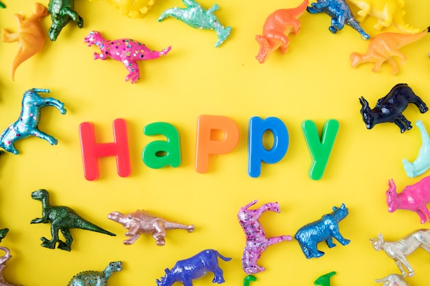 Vários figuras de brinquedo animal fundo com a palavra feliz