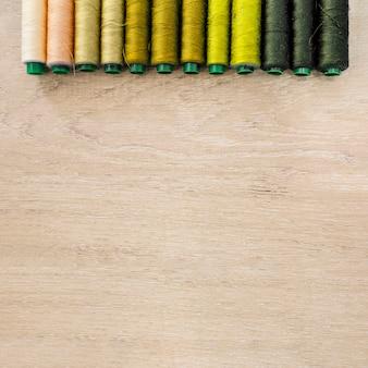 Vários fios coloridos dispostos em uma fileira no fundo de madeira