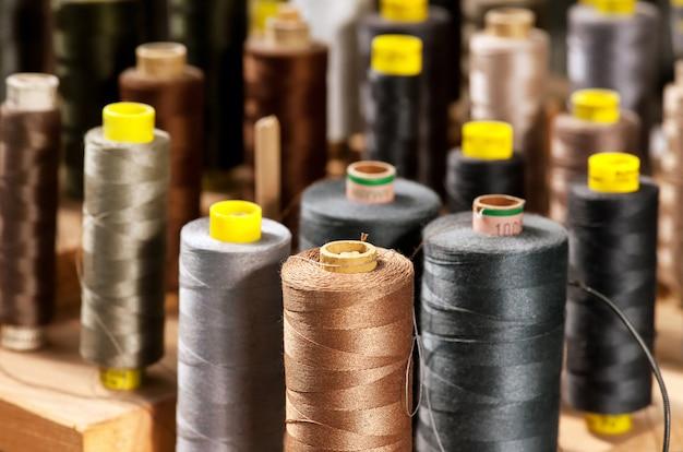 Vários fios coloridos em bobinas em um alfaiate