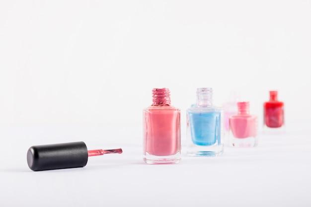 Vários frascos de esmaltes coloridos, isolados no fundo branco