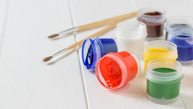 Vários frascos de guache virados e um pincel em uma mesa de madeira branca