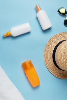 Vários frascos de loção e cremes para proteção com conchas e chapéu