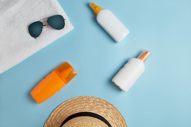 Vários frascos de loção e cremes para proteção com óculos escuros e chapéu
