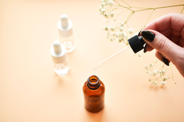Vários frascos de óleo cosmético na pipeta de mão da menina. produto cosmético elegante para tratamento antienvelhecimento. vista plana leiga, superior. Foto Premium