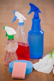 Vários frascos de spray, esponja e luva no piso de madeira