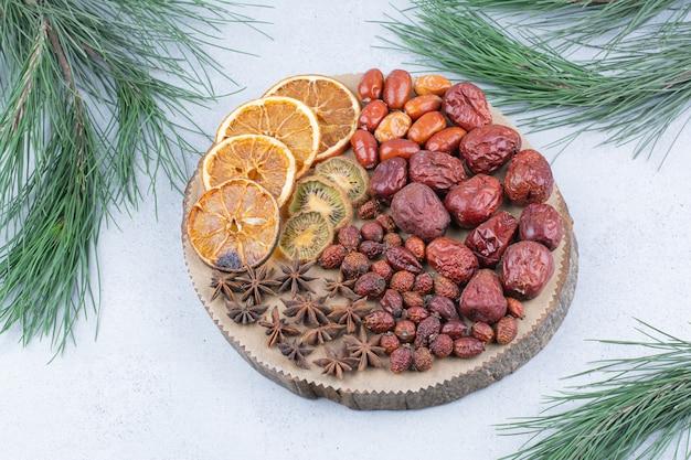 Vários frutos secos e cravos na peça de madeira.