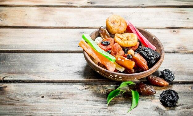 Vários frutos secos em uma tigela sobre uma mesa de madeira.