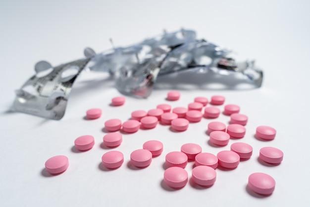 Vários grandes comprimidos rosa brilhantes derramados de um frasco de vidro no fundo branco