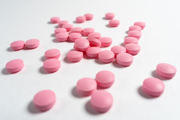 Vários grandes comprimidos rosa brilhantes derramaram de um frasco de vidro no fundo branco.