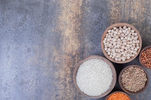 Vários grãos crus, lentilhas e arroz em tigelas de madeira.