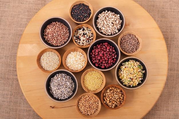 Vários grãos e cereais em pequenas tigelas na bandeja de madeira