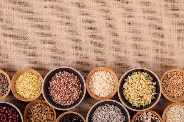 Vários grãos e cereais em pequenas tigelas no fundo do cânhamo