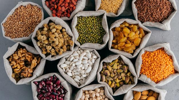 Vários grãos e frutos secos em sacos de juta no mercado param. vista do topo. conjunto de produtos saudáveis orgânicos. conceito de alimentação saudável