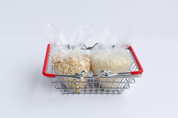 Vários grãos em pacotes na cesta de compras. arroz e aveia
