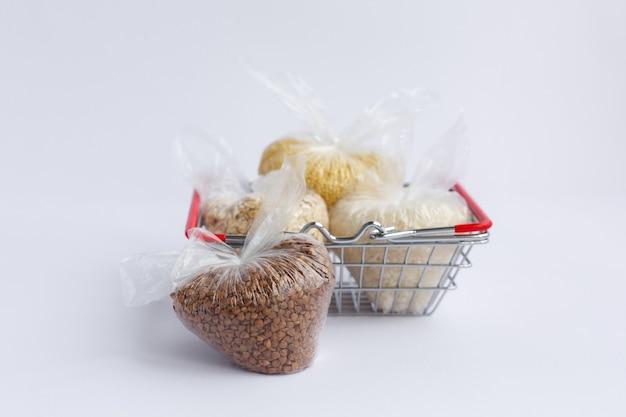 Vários grãos em pacotes na cesta de compras. arroz e farinha de aveia, trigo sarraceno e painço