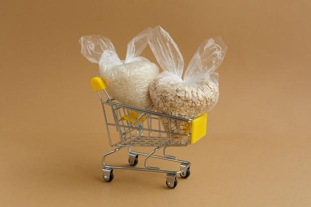 Vários grãos em pacotes no carrinho de supermercado. arroz e aveia