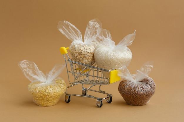 Vários grãos em pacotes no carrinho de supermercado. arroz e farinha de aveia, trigo sarraceno e painço