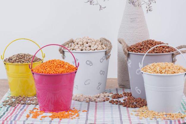 Vários grãos secos em baldes coloridos.