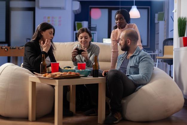 Vários grupos étnicos de colegas de trabalho jogam no console enquanto seguram o joystick. amigos diversos alegres desfrutam de uma competição divertida no computador da tv enquanto tomam lanches e cerveja da mesa