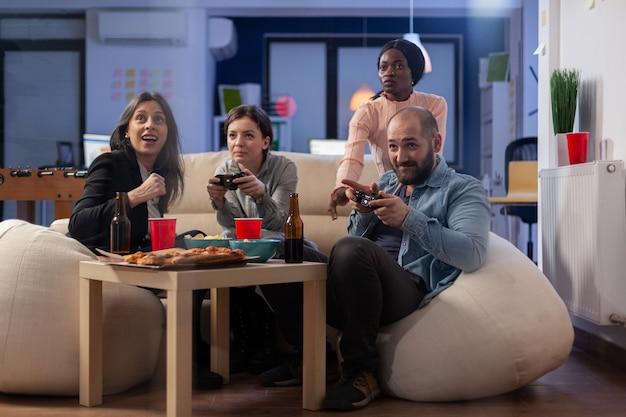 Vários grupos étnicos de colegas de trabalho jogam no console