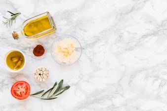 Vários ingredientes com óleo no fundo de mármore branco