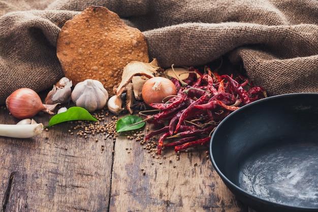 Vários ingredientes usados para fazer comida asiática são colocados ao lado da panela sobre a mesa de madeira.