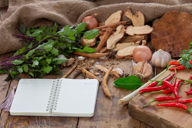 Vários ingredientes usados para fazer comida asiática são colocados junto com os cadernos sobre a mesa de madeira.