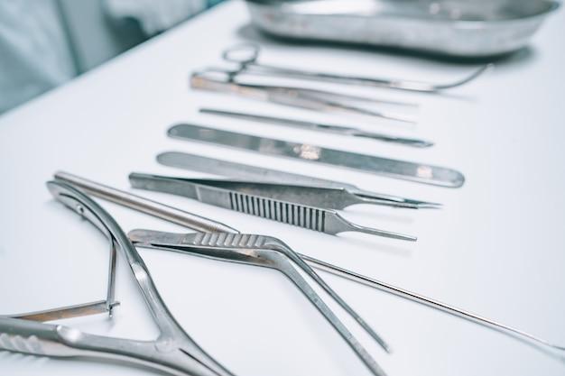 Vários instrumentos cirúrgicos estão sobre uma mesa branca