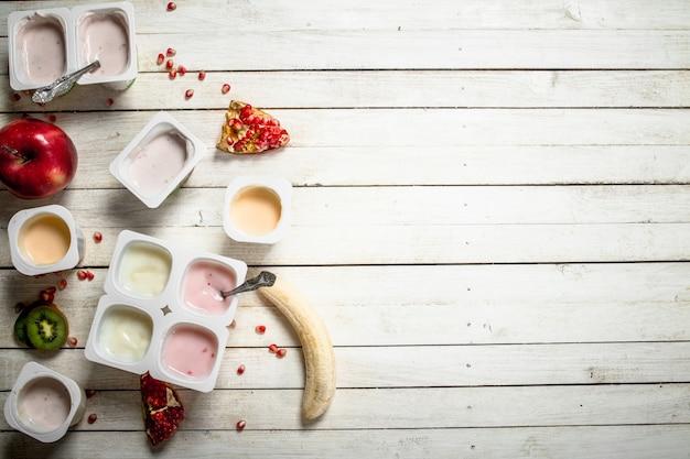 Vários iogurtes de frutas. em uma mesa de madeira branca.