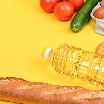Vários itens alimentares, frutas e legumes em uma superfície amarela