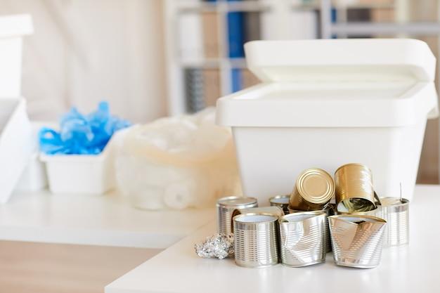 Vários itens de lixo classificados por tipo de material e prontos para reciclagem no interior do escritório, foco em latas de metal descartadas em primeiro plano
