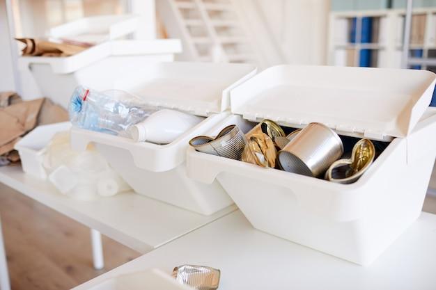 Vários itens de lixo classificados por tipo de material e prontos para reciclagem no interior do escritório, foco em latas de metal em primeiro plano