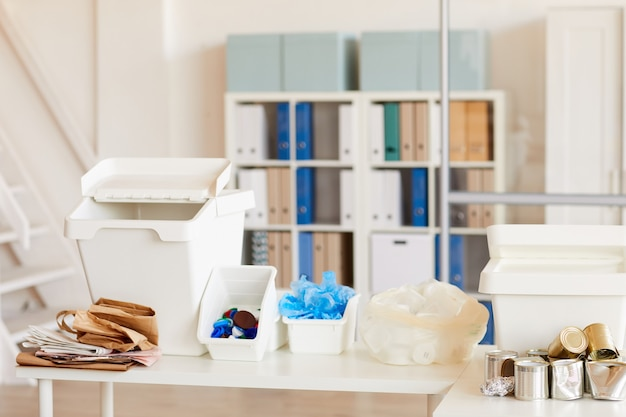 Vários itens de lixo classificados por tipo de material e prontos para reciclagem no interior do escritório