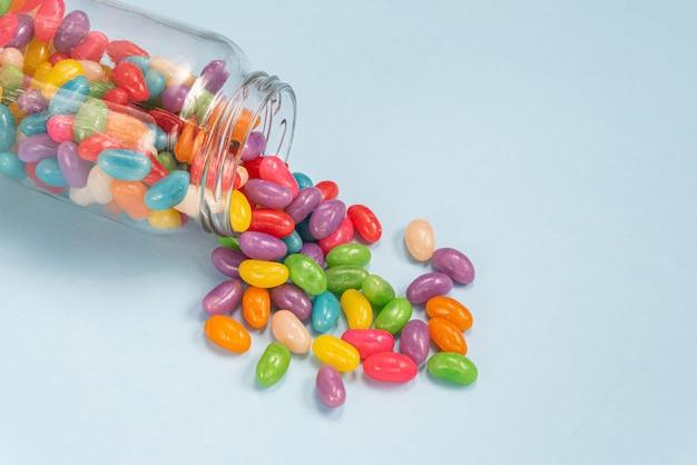 Vários jelly beans na superfície azul dentro do pote de vidro