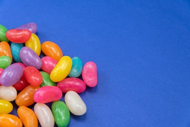 Vários jelly beans sobre a superfície azul