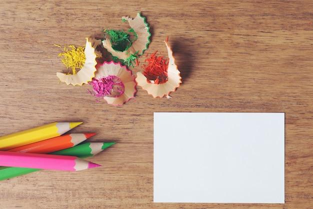 Vários lápis de cor na mesa de madeira.
